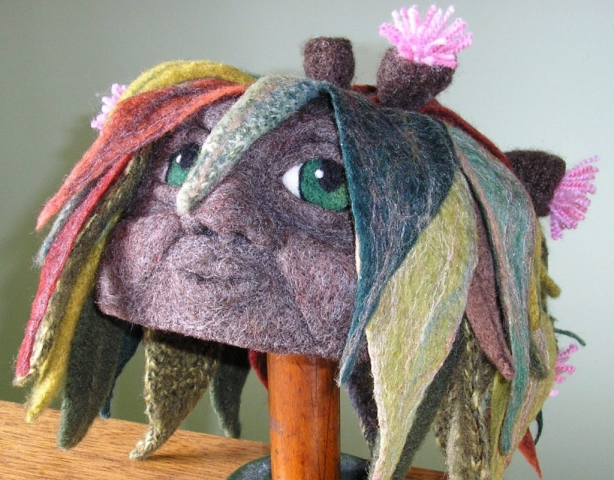 Wearable art beanie depicting a eucalypt man with felted leaves and gum blossoms