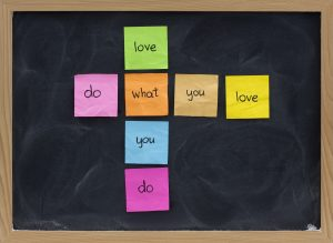 do what you love, love what you do - happy life and work concept presented on blackboard with colorful sticky notes, white chalk smudges