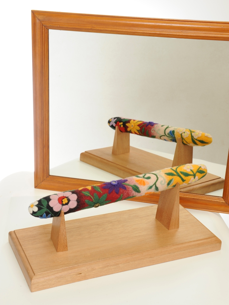 Felted sculpture depicting a talking stick, embroidered in floral patterns.