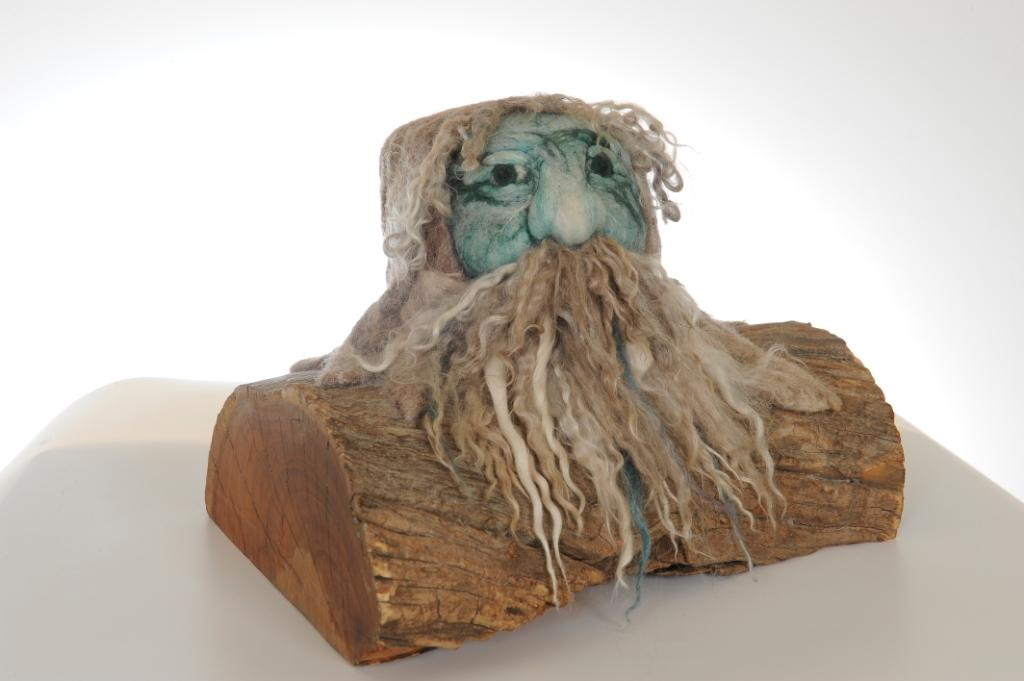 Felted sculpture of a man of the forest mounted on a natural timber base.