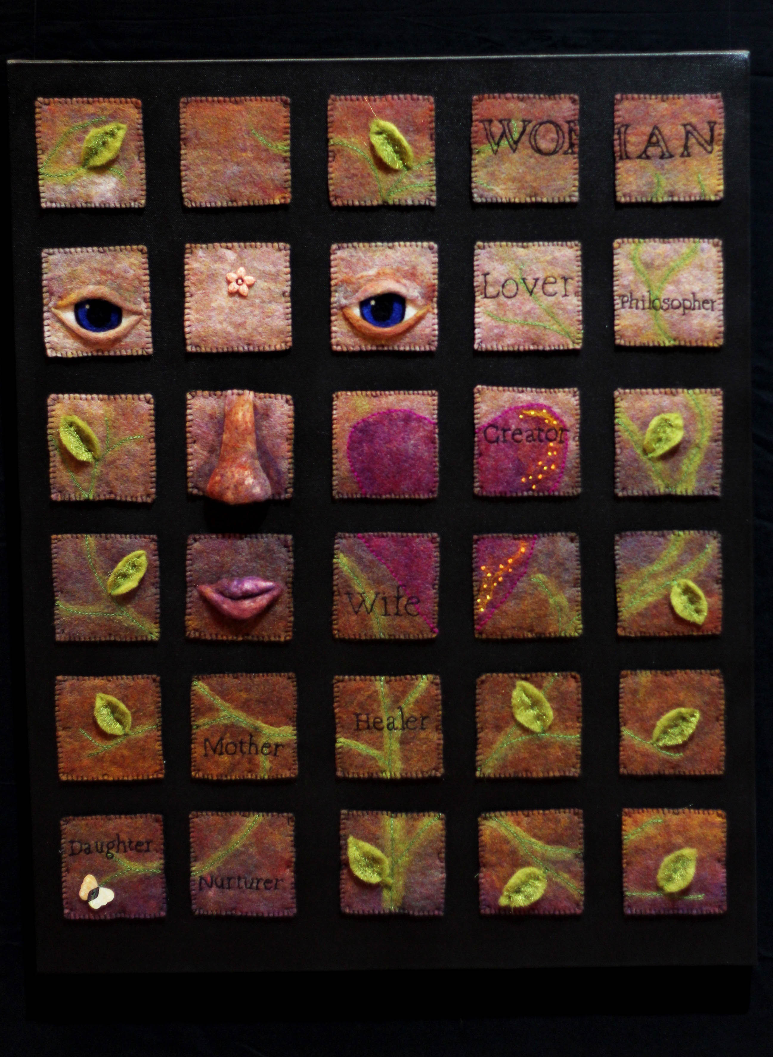 Black canvas with small squares of felt depicting a female face and the various roles a woman takes in life.