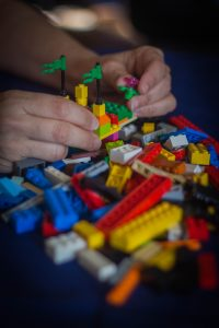 hands building with Lego